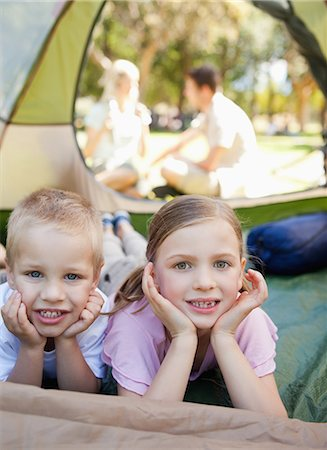 Two smiling children lie down in the tent together with their parents outside Stock Photo - Premium Royalty-Free, Code: 6109-06003914