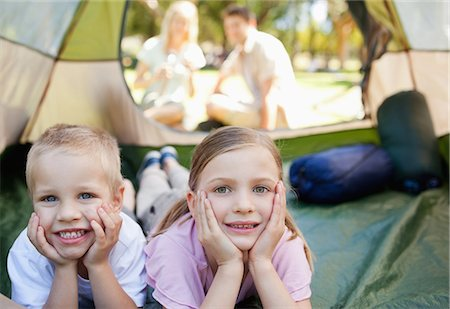 A smiling bother and sister lie down inside of the tent while their parents sit outside looking in Stock Photo - Premium Royalty-Free, Code: 6109-06003915