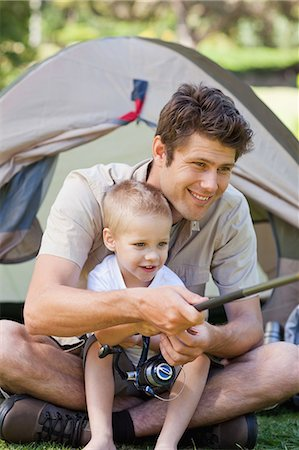 A close up shot of a dad and his boy fishing by the tent Stock Photo - Premium Royalty-Free, Code: 6109-06003923