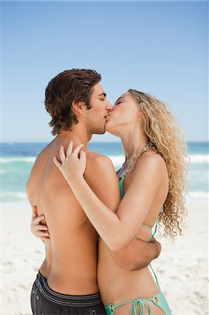 Young couple standing on the beach while kissing each other Stock Photo - Premium Royalty-Free, Code: 6109-06004084