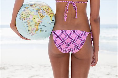 Young woman holding a globe beach ball while standing in front of the ocean Stock Photo - Premium Royalty-Free, Code: 6109-06004140