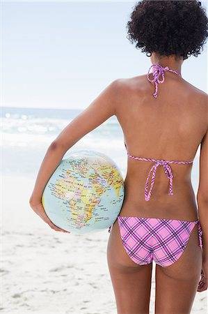 Rear view of a young woman standing in front of the ocean with a globe beach ball Stock Photo - Premium Royalty-Free, Code: 6109-06004141