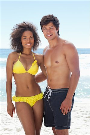 A man and a woman wearing swimsuits while smiling as they hold each other on the beach Stock Photo - Premium Royalty-Free, Code: 6109-06004177