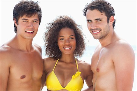 sexy black women in bikinis - Two men and a woman wearing swimsuits while smiling as they embrace each other Stock Photo - Premium Royalty-Free, Code: 6109-06004175