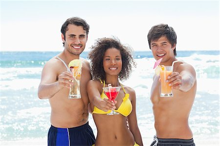 Two men and a woman in swimsuits smiling as they offer cocktails on a beach Stock Photo - Premium Royalty-Free, Code: 6109-06004183