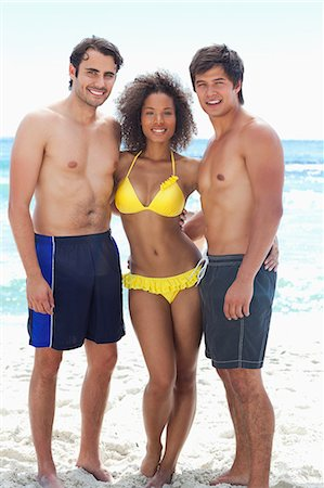 Woman wearing a yellow bikini while smiling with her arms around two men as they stand on a beach Stock Photo - Premium Royalty-Free, Code: 6109-06004181