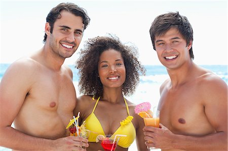 sexy black women in bikinis - Two men and a woman wearing swimsuits while smiling as they hold cocktails on a beach Stock Photo - Premium Royalty-Free, Code: 6109-06004182