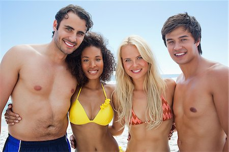 sexy black women in bikinis - Two men and two women in swimwear smiling as they embrace each other with the sky in the background Stock Photo - Premium Royalty-Free, Code: 6109-06004188