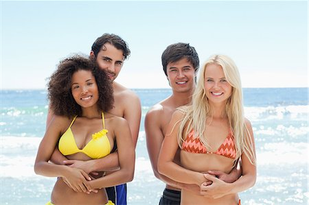 sexy black women in bikinis - Two men holding their partners as they stand by the water in swimwear Stock Photo - Premium Royalty-Free, Code: 6109-06004189