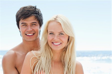 sexy black women in bikinis - Man and a woman smiling as they embrace each other by the water while wearing swimsuits Stock Photo - Premium Royalty-Free, Code: 6109-06004193