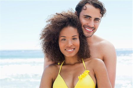 sexy black women in bikinis - Man in swimwear happily smiling as he holds his friend by the water Stock Photo - Premium Royalty-Free, Code: 6109-06004192