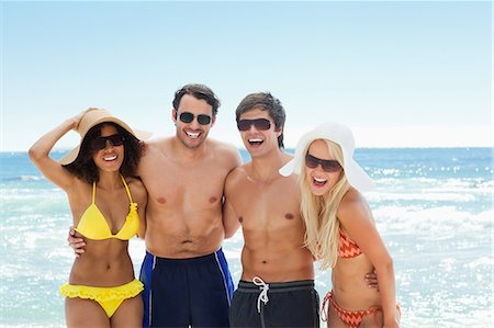 Two men and two women wearing swimwear as they hold each other by the water Stock Photo - Premium Royalty-Free, Code: 6109-06004194