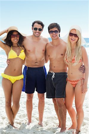 Two men and two women in swimsuits smaile as they put their arms around each other on the beach Stock Photo - Premium Royalty-Free, Code: 6109-06004195