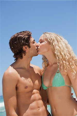 Young couple kissing each other while standing in front of the ocean Stock Photo - Premium Royalty-Free, Code: 6109-06004112