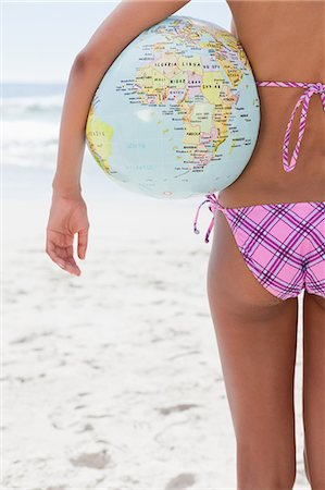 Rear view of a young woman holding a globe beach ball while standing on the beach Stock Photo - Premium Royalty-Free, Code: 6109-06004139