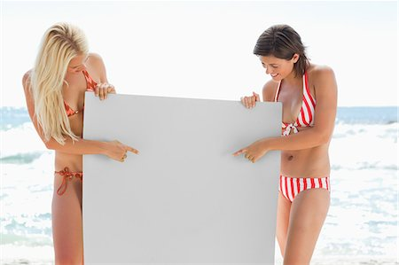 Two women in bikinis pointing at a blank poster as they hold it by the sea Stock Photo - Premium Royalty-Free, Code: 6109-06004241