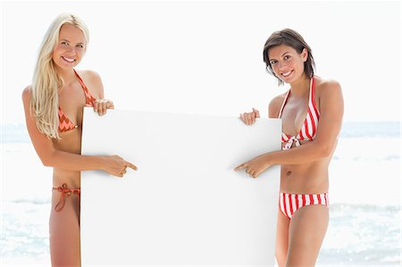 poster - Two women in bikinis smiling while holding a large white poster and pointing at it by the sea Stock Photo - Premium Royalty-Free, Code: 6109-06004242
