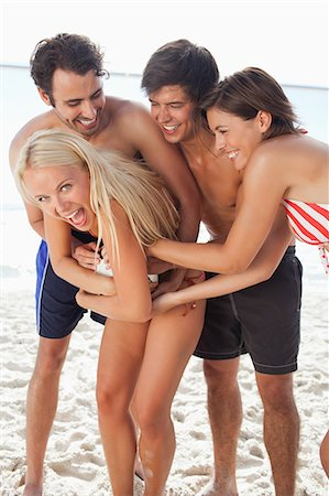 Two men and two women in swimsuits laughing as they tussle for a football on the beach Stock Photo - Premium Royalty-Free, Code: 6109-06004247