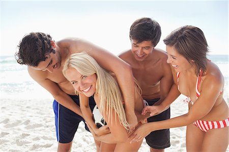 Woman in a bikini smiling as she tussles with her friends for a white football on the beach Stock Photo - Premium Royalty-Free, Code: 6109-06004246