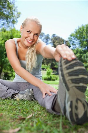 flexible (people or objects with physical bendability) - Smiling young sportswoman doing stretches in the park Stock Photo - Premium Royalty-Free, Code: 6109-06004293