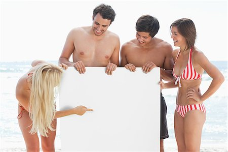 Woman in a bikini pointing at a large blank poster while holding it with her three friends Stock Photo - Premium Royalty-Free, Code: 6109-06004233