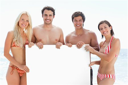 poster - Two men and two women smiling as they hold a blank poster between them by the sea Stock Photo - Premium Royalty-Free, Code: 6109-06004235