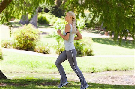 Side view of young female jogger in the park Stock Photo - Premium Royalty-Free, Code: 6109-06004304