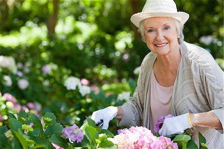Woman smiling and looking ahead while pruning pink flowers in a garden Stock Photo - Premium Royalty-Free, Code: 6109-06004584