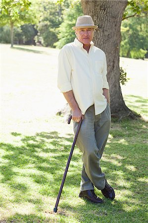 stick - Man leaning on a cane while standing with his legs crossed in a park Stock Photo - Premium Royalty-Free, Code: 6109-06004698