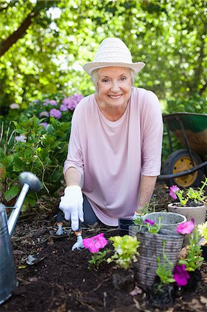 Woman smiling happily while planting pink flowers in her garden Stock Photo - Premium Royalty-Free, Code: 6109-06004610