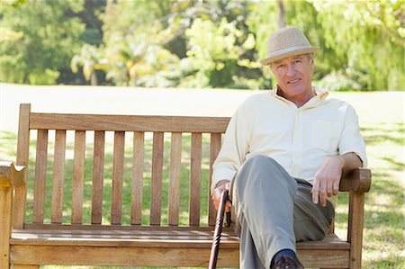 Man holding a cane and sitting on a bench while he looks ahead of him in a park Stock Photo - Premium Royalty-Free, Code: 6109-06004704