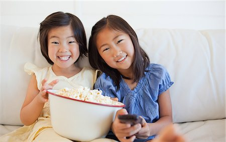 Two sisters enjoying popcorn and television while laughing together. Stock Photo - Premium Royalty-Free, Code: 6109-06004846