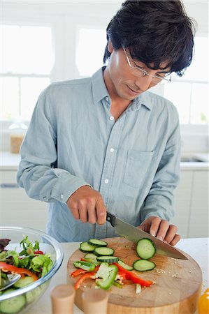 A man cuts through a cucumber turing it into slices to add to a salad Stock Photo - Premium Royalty-Free, Code: 6109-06004960