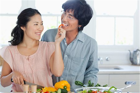 A husband and wife work and eat in the kitchen making a salad and eating pepper Stock Photo - Premium Royalty-Free, Code: 6109-06004975