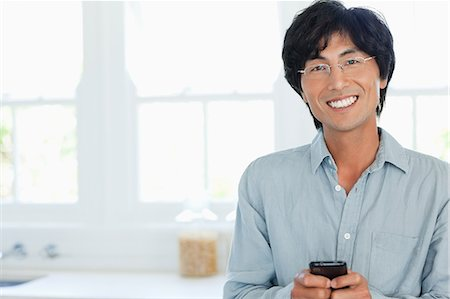 A smiling man uses his phone to send a text while looking straight ahead Stock Photo - Premium Royalty-Free, Code: 6109-06004983