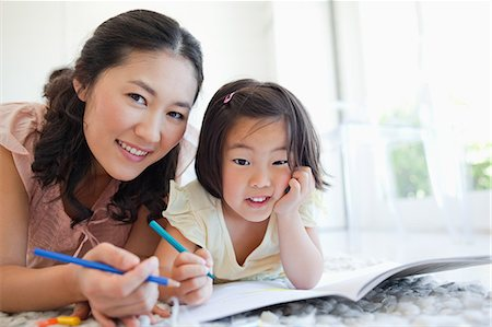 A mother and daughter smiling and looking ahead as they stop colouring for a moment. Stock Photo - Premium Royalty-Free, Code: 6109-06004903