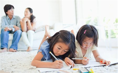 The parents chat on the couch as the girls lie on the ground and colour in their colouring books Stock Photo - Premium Royalty-Free, Code: 6109-06004901