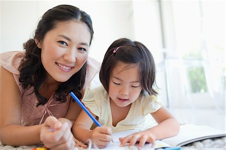 A mother looks up and smiles while her daughter continues to colour Stock Photo - Premium Royalty-Free, Code: 6109-06004904