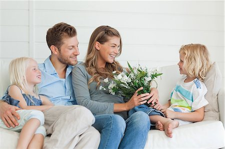 A son hands her mother a bouquet of flowers as the family sits on the couch Stock Photo - Premium Royalty-Free, Code: 6109-06005062