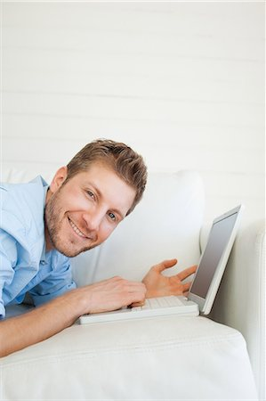 A close up shot of a man using his laptop as he smiles and lies across the couch Fotografie stock - Premium Royalty-Free, Codice: 6109-06005077