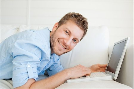 A man using his laptop as he lies across the couch and smiles. Fotografie stock - Premium Royalty-Free, Codice: 6109-06005076