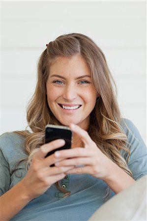 A woman looking straight ahead and smiling as she uses her mobile phone to send a text Stock Photo - Premium Royalty-Free, Code: 6109-06005033