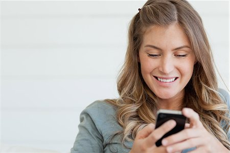 A smiling woman who is sitting while she uses her phone to send a text message Stock Photo - Premium Royalty-Free, Code: 6109-06005031