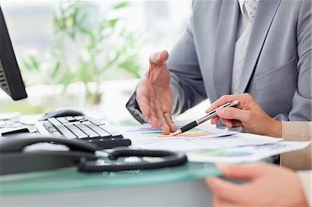 Close-up of people working on figures in an office Stock Photo - Premium Royalty-Free, Code: 6109-06005258