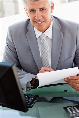 report - Portrait of a businessman signing files in a brigh office Stock Photo - Premium Royalty-Free, Code: 6109-06005342