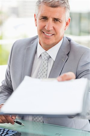 Portrait of a boss giving a file in a bright office Stock Photo - Premium Royalty-Free, Code: 6109-06005345