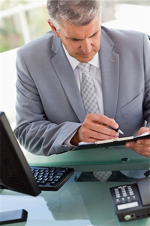 report - Businessman signing files in a brigh office Stock Photo - Premium Royalty-Free, Code: 6109-06005339