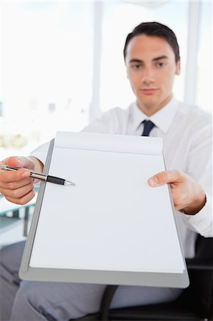 Businessman showing a file in a bright office Stock Photo - Premium Royalty-Free, Code: 6109-06005568