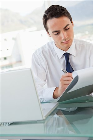 report - Businessman taking notes on a paper in a bright office Stock Photo - Premium Royalty-Free, Code: 6109-06005574