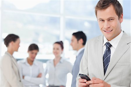 staff - Smiling young salesman with his mobile phone and colleagues behind him Stock Photo - Premium Royalty-Free, Code: 6109-06005675